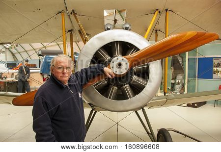 MONTROSE, SCOTLAND, UK - Apr 9, 2014: Daniel Paton the curator at Montrose Air Station Museum and an expert on the Royal Flying Corps officers and airmen from No. 2 Squadron pictured in front of a Sopwith biplane.