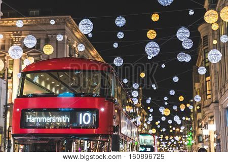 Red double decker bus in London during Christmas time. Lights and decorations over the famous London street reflecting on the bus surface. Travel and tourism concpets