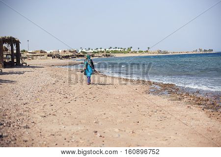 Egypt Sharm el sheikh - august 2016: one muslim young woman walking on the sea shore