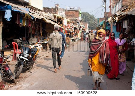CHITRAKOOT, INDIA - DEC 30, 2012 : Poor people walking on the Indian street at the beautiful sunny day on December 30, 2012 in India. Population of Chitrakoot is 22294. Males constitute 57 perc