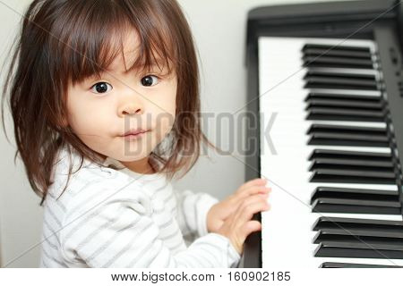 Japanese girl playing a piano (2 years old)
