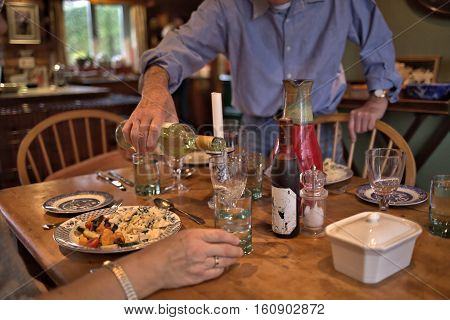 Man in blue shirt pouring white wine to glass during dinner in house. Posh home interior with homey atmosphere at lunch poster