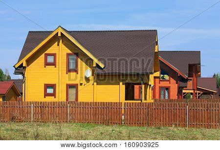 Settlement of wooden cottages of brown color on the edge of the forest