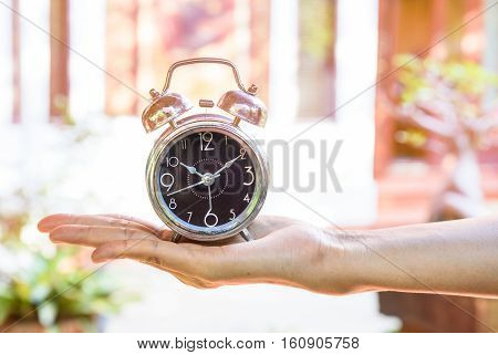 Time and priorities conceptual image.Clock on hand