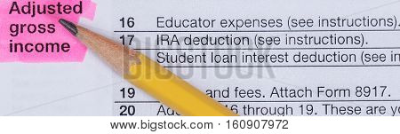 Tax concept with pencil tip pointing towards highlighted adjusted gross income.