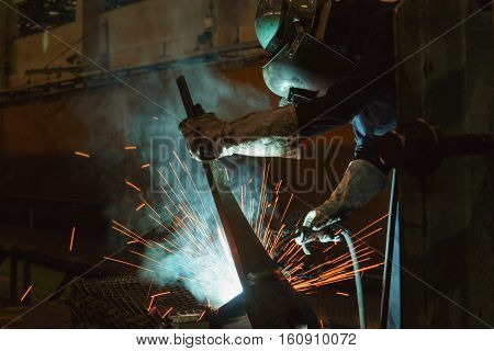 Welder of Metal Welding with sparks and smoke