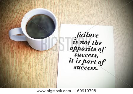 Inspirational Motivating Quote On Paper With Black Coffee On The Table. Failure Is Not The Opposite