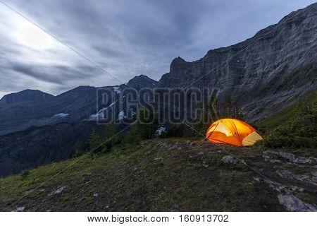 Illuminated tent camping on ridgeline of a mountain