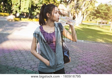 Portrait Of Young Beautiful Woman In Sport Wearing Drinking Water