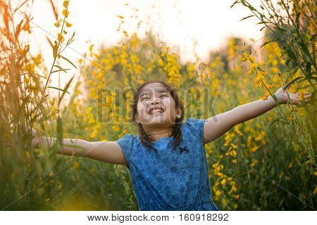 Happy Asian girl feeling freedom in the flower field