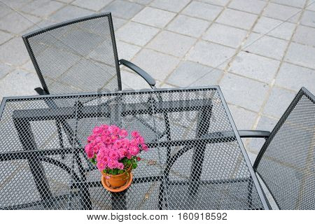 Cast iron table and chairs on a patio, with pot of pink flowers