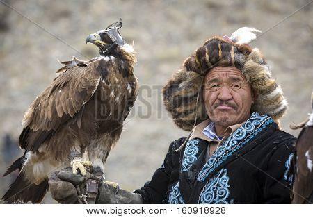 Bayan Ulgii Mongolia October 4th 2015: Eagle hunter riding a horse with his Altai Golden Eagle