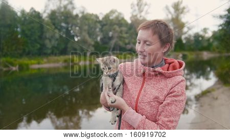 Happy young Woman shows the British Shorthair Tabby cat near forest river, outdoor, camping