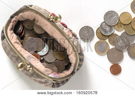 coins in handmade purse on white background