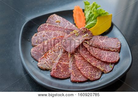Raw beef slice for barbecue or Japanese style yakiniku on black plate.