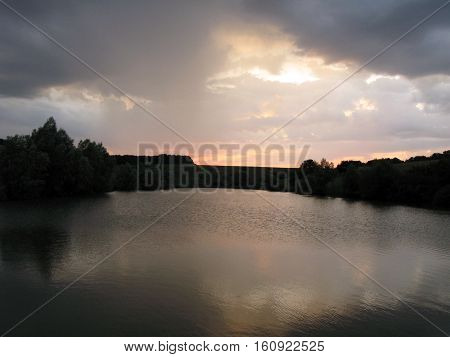Summer evening, small lake in a small valley and small trees on banks
