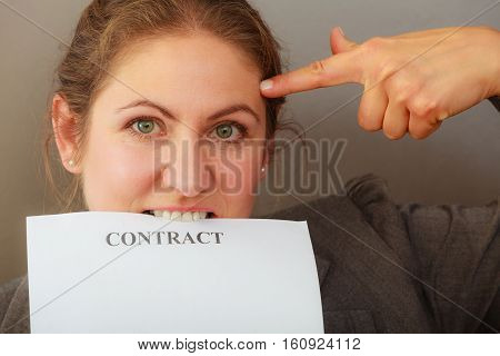 Stress at work. Contracts and agreements concept. Middle aged stressed angry upset business woman biting contract agreement. Face emotion expression. Human on deadline reaction.