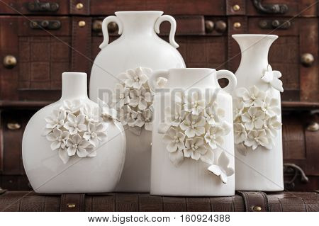 Different Decorative White Vases On Brown Background