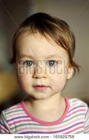 Portrait of white baby girl with grey eyes. Curious baby on blurred background. mother`s love. Concept of calmness, care, innocence.
