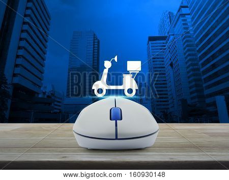 Wireless computer mouse with motor bike icon on wooden table over modern city tower Business internet delivery service concept