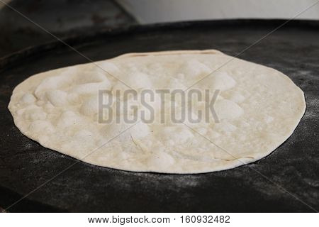A slice of dough baked on the Lebanese traditional saj to become pita bread.