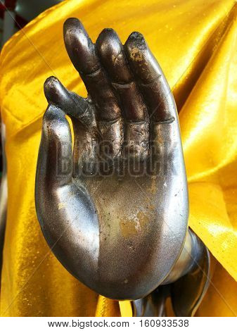 Buddha statue's hand in a gesture of meditation and blessing.
