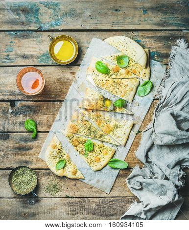 Homemade Italian focaccia flatbread cut into pieces with herbs, fresh basil leaves, olive oil in cup and glass of rose wine over rustic wooden background, top view