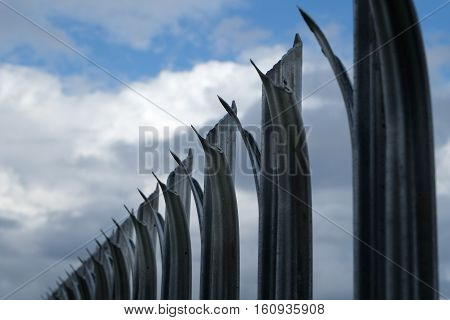 Steel sharp top to security fence against sky.