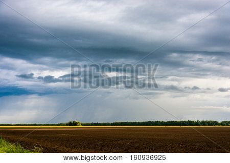Rain Clouds And Plowed Field.