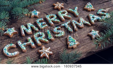 Wording Merry Christmas from homemade gingerbread cookies with icing on old wooden background with fir tree. Christmas moody style greetings card. Happy New Year. Christmas concept. Selective focus.