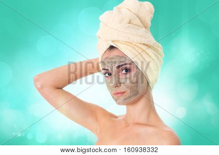 gorgeous girl takes care her skin with cleansing mask on face and towel on head isolated on white background. Health care concept. Body care concept. Young woman with healthy skin.