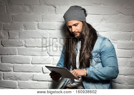Portrait photo of rocker guy in sunglasses and woolly hat standing against brick wall using tablet computer.