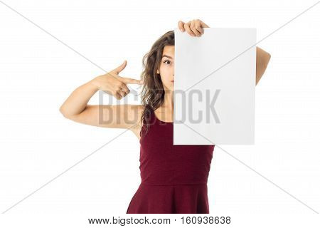 cutie young brunette girl in red dress with white placard in hands isolated