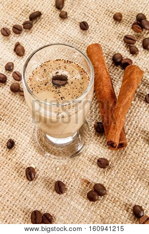 coffee cream liqueur in a glass with coffee beans and cinnamon sticks on jute