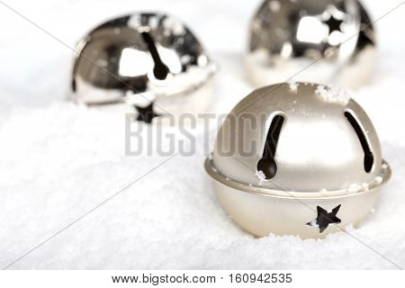 Silver jingle bells in the snow. Seasonal decorative Christmas themed image.