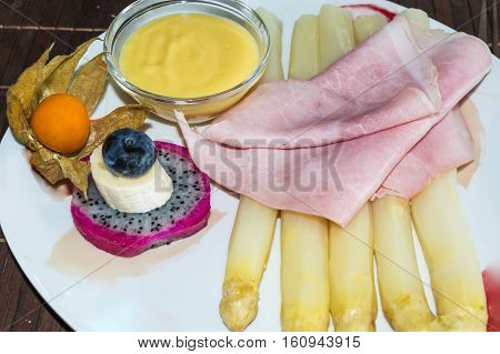 Simple asparagus dish with boiled ham and sauce garnished on a white plate.