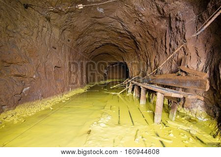 Old abandoned shaft mine tunnel with sulfur dirt