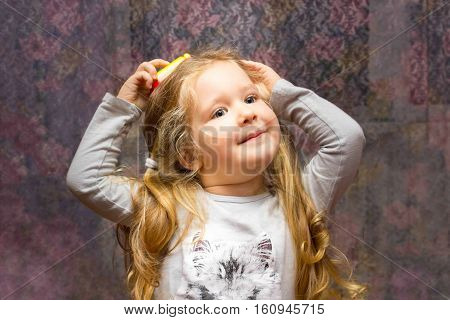 Little girl with a toy as mobile phone at home
