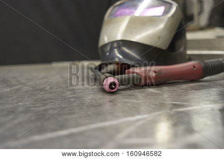 Welder Equipment Tig Torch With Welder Shield On A Steel Plate