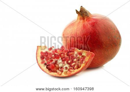 one whole pomegranate(Punica granatum)and a cut piece on a white background