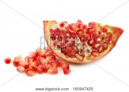 pomegranate piece(Punica granatum) and some seeds on a white background