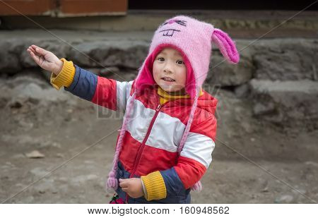 SIKKIM, INDIA - DECEMBER 03, 2016: Cute expressive Indian kid in winter wear at Lachung, Sikkim, India.