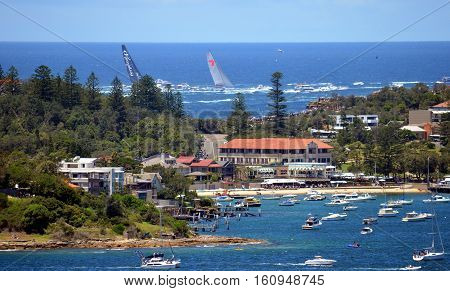 Sydney Australia - December 26 2013. Looking over Watson Bay and The Gap Wild Oats and Perpetual 8 leading the yacht race. Sydney to Hobart Yacht Race on Boxing Day.