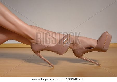 woman shapely legs wearing brown lacquered high heel shoes. Close up view