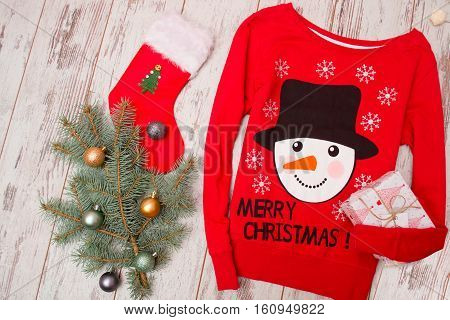 Red sweater with a snowman on a wooden background. Fur-tree branch with Christmas decorations stocking gift