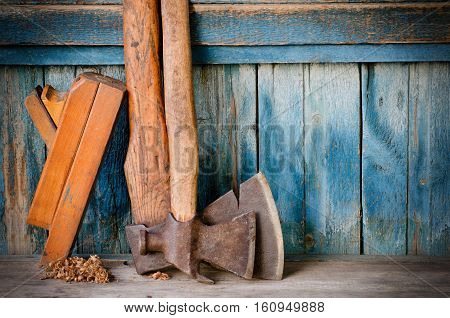 Axes planer shavings chips on the old blue wooden background