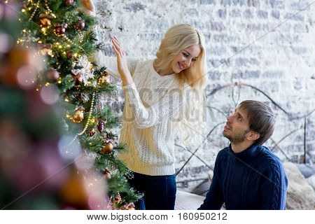 Happy Couple Of Lovers In Pullovers Decorating Christmas Tree