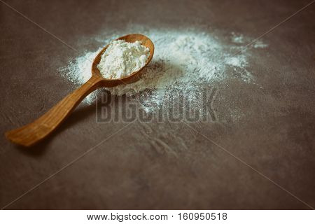 Dark and moody baking background rustic wooden spoon with a flour on a dark surface selective focus on a flour hip