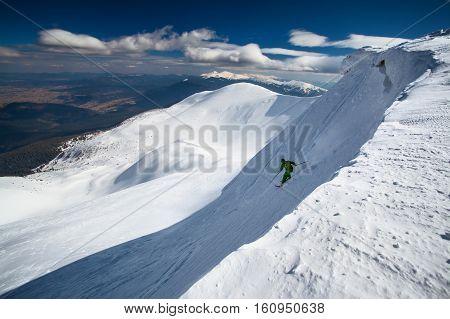 Winter ski freeride in mountain powder snow. Skier rides downhill in Carpathian mountains. Hoverla peak on background.