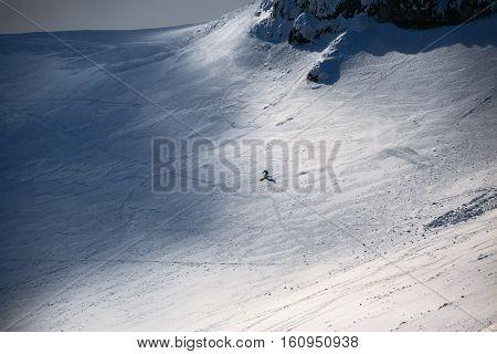 Freeride ski in Carpathian mountains peak on background. Skier skiing in winter mountains.